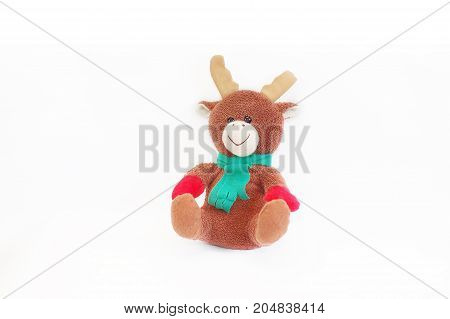 Soft toy brown deer with horns in a green scarf. White background. Isolated