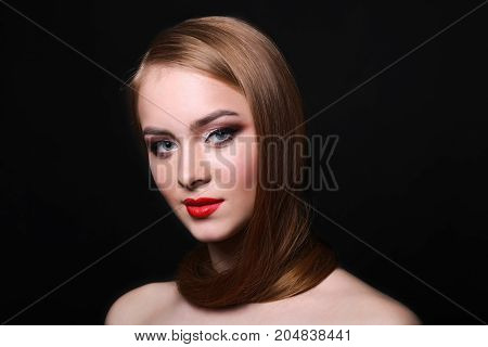 Beautiful woman model on black background with copy space, fashion shooting. Girl with makeup, perfect skin and hair posing to camera at studio