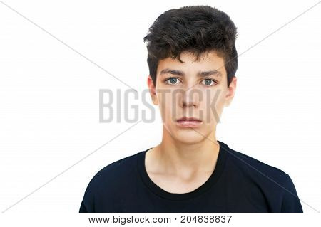 Handsome teenager in a black shirt on a white background. He has sad eyes and an inquisitive look. Isolated