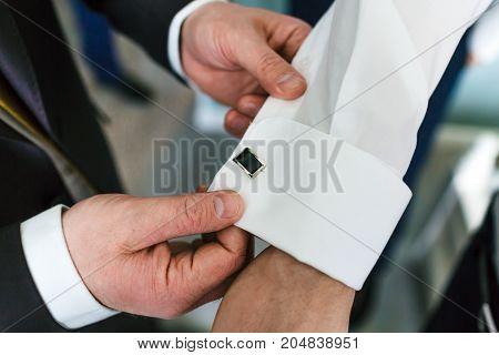 Groom's friend helps fasten cufflinks on groom's sleeve. Wedding. Close-up