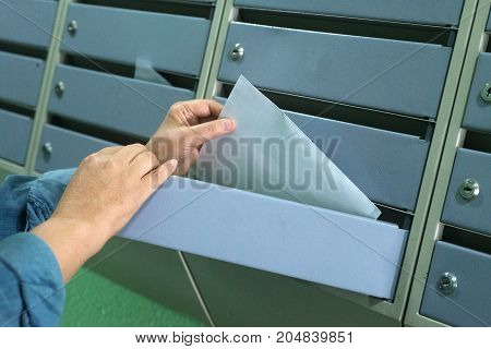 women's hands pull out a white envelope from the mailbox