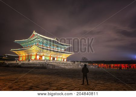 Gyeongbokgung Palace At Night In South Korea with the name of the palace 'Gyeongbokgung' on a sign