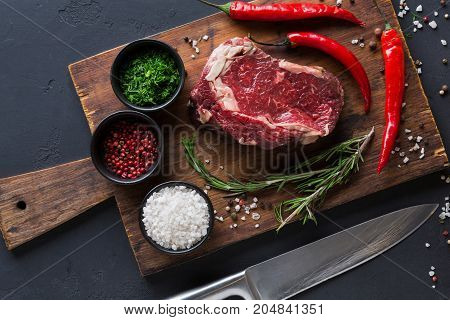 Raw rib eye steak with herbs and spices. Cooking ingredients for restaurant dish. Fresh meat with chilli on wooden desk on black background, top view