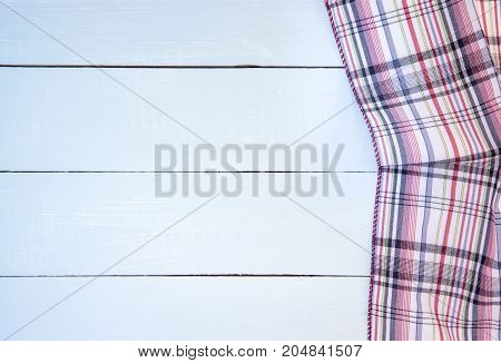 checkered tablecloth on blue wooden table background