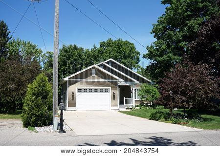 BAY VIEW, MICHIGAN / UNITED STATES - JUNE 13, 2017: A single family home, with an attached garage and a driveway.