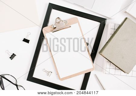 Modern home office desktop with clipboard pen book. Flat lay top view business concept.