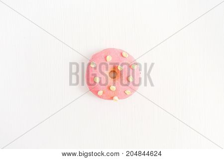 One pink donut on white background. Flat lay top view minimal concept.