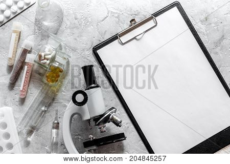 Microscope and tablet on grey stone background top view.