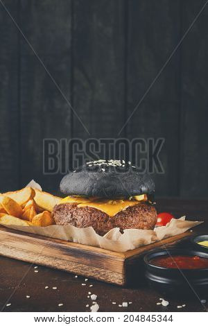 Black bun burger with potato wedges and sauces on wooden tray copy space. Appetizing cheeseburger with cutlet, fast food concept