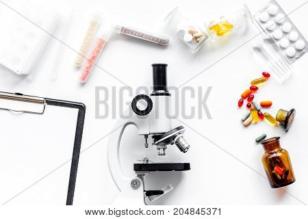 Do medcal tests. Microscope, tablet, pills and test tube on white background top view.