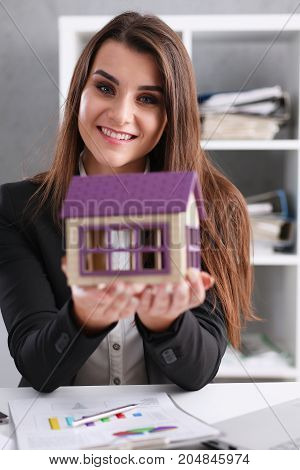 Businesswoman In The Office Holds A Miniature Toy House In Her Hand