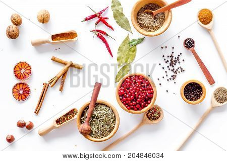 Colorful dry herbs and spices for cooking food on white kitchen table background top view pattern
