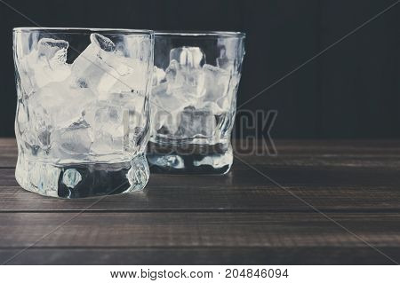 Glasses with ice cubes on dark background. Cold summer cocktail preparing, refreshment concept