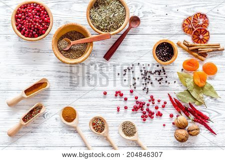 Kitchen table with spices and dry herbs on light wooden kitchen desk background top view pattern