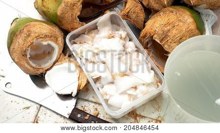 Peeled the Thai coconut for eat and drink The kitchen equipment has chopper knife spoon plastic box and jar on the floor.