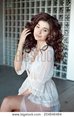 Sexy girl in a white transparent peignoir. Model with medium-brown curly hair. Luxurious body
