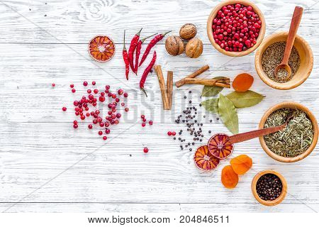 Colorful dry herbs and spices for cooking food on light wooden kitchen table background top view space for text