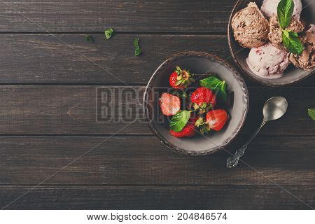 Portion of chocolate and berry ice cream scoops and strawberry on rustic wooden background, copy space. Delicious sweet summer dessert, top view