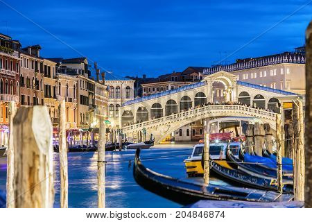 Venice Italy. Rialto bridge and Grand Canal at twilight blue hour. Gondolas on the foreground. Tourism and travel concept