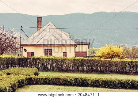 Old rail station in the natural landscape. Historic building in picturesque country. Yellow photo filter.