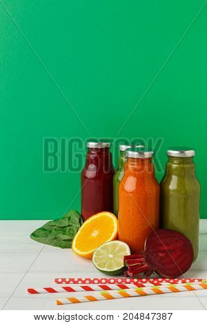 Healthy food. Assortment of fruit and vegetables detox smoothies with ingredients in glass bottles on pastel green wall background, copy space.