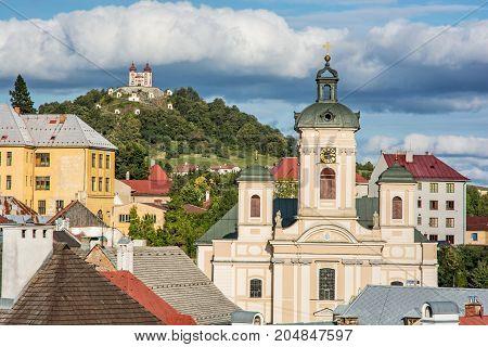 Calvary and Church of the assumption in Banska Stiavnica Slovak republic. Sunset urban scene. Travel destination.