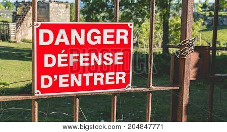 Red Sign Placed On A Rusty Gate Or It Is Written In French Danger Defended To Enter