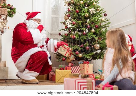 Hush-hush. Mysterious Santa Claus is laying present boxes under Christmas tree. He is gesturing secretly to curious girl, who is sitting on floor