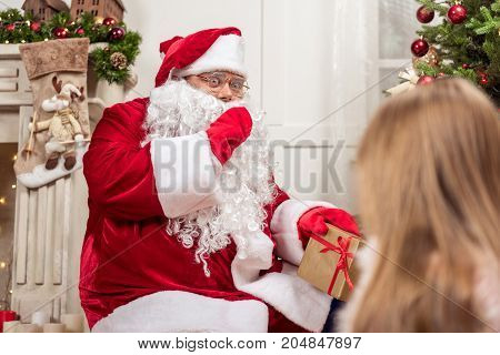Please, keep my secret. Surprised fat bearded man in red and white costume is putting gifts under fir-tree secretly. Curious girl is looking at Santa