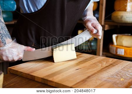Cutting hard cheese, pecorino cheese in grocery shop, closeup