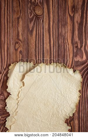 Ancient Papyrus On A Wooden Table, Background Of Clean Paper And Wood