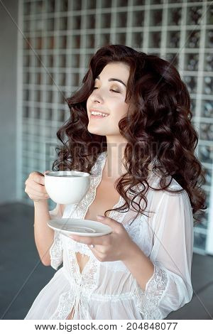 Attractive smiling girl enjoying a cup of coffee in a white transparent peignoir. Model with medium-brown curly hair and nice body. Half-length shot.