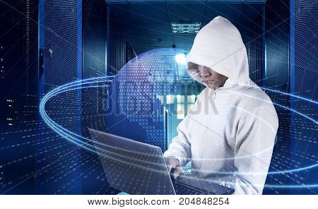 hacker with a laptop among the servers in your data center on the background of the hologram cyber attack and the planet earth.