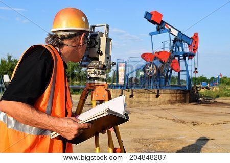 A male land surveyor engineer at work on an east European oil well