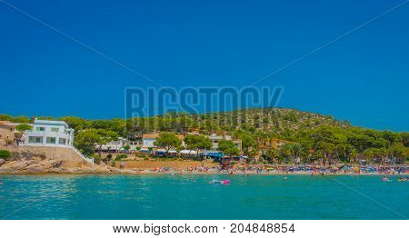 Beautiful sunny day in Sant Elm, with a beautiful blue water in Majorca, with some building in the horizont and people enjoying the weather, in Spain.