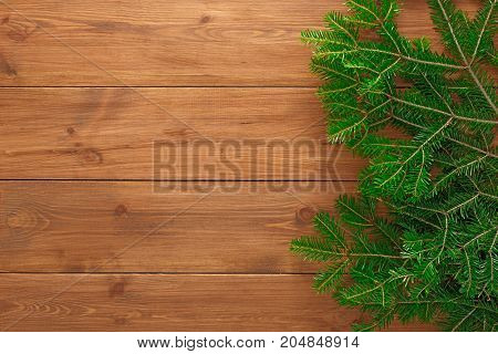 Christmas decoration, frame concept background, top view on natural rustic wood table surface. Fir tree branches border with copy space