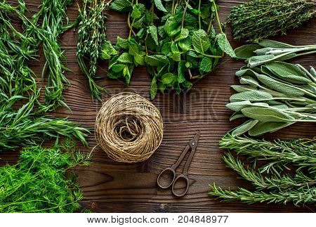 making spices with fresh herbs and greenery for cooking on wooden kitchen table background top view