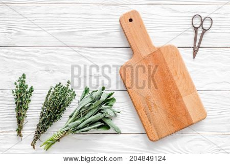making spices with fresh herbs and greenery for cooking on white wooden kitchen table background top view mockup