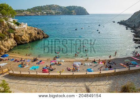 PORT D ANDRATX, SPAIN - AUGUST 18 2017: Unidentified people enjoying the beach in Andratx port in Mallorca balearic islands, in a sunny day, Spain.