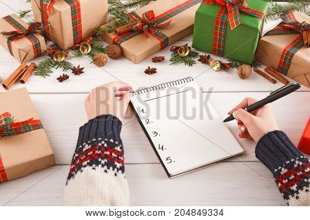 Christmas online shopping. Smartphone, credit card and presents list with copy space on wooden table with gift boxes border. Top view, preparing for winter holidays concept