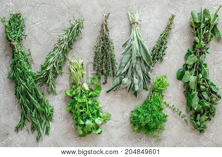 making spices with fresh herbs and greenery for cooking on stone kitchen table background top view pattern