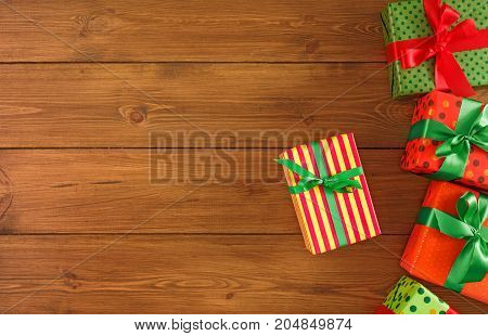 Creative presents in colored paper decorated for any holiday concept. Gift boxes, top view with copy space on wood table background.