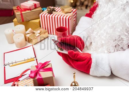 Close up of Santa Claus arms using digital tablet while sitting at desk