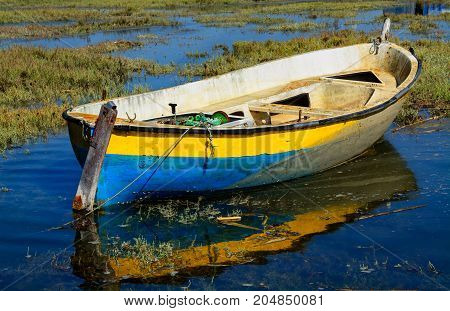 abandoned old fishing boat in calm water in comporta alentejo Portugal.