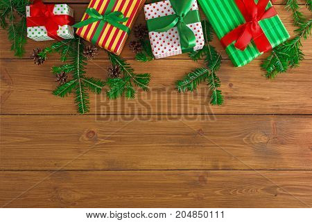 Colorful striped gift boxes and fir tree twigs border, top view with copy space on wooden background. Frame of colored packages with red, green ribbon bows for christmas, valentine day or birthday