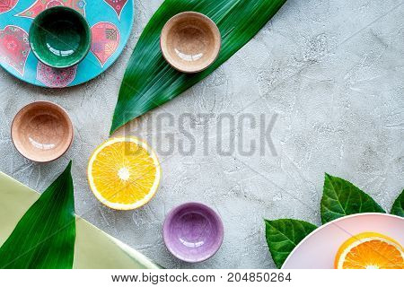 Tableware pattern. Cups and plates decorated by exotic leaves and fruits on grey background top view.