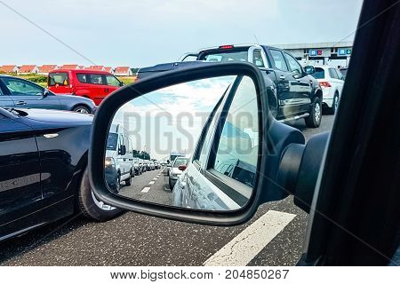 Traffic jam on a highway in the car rearview mirror