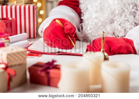 Close up of male hands in red gloves writing in notebook by pen. Santa Claus is sitting at desk near various presents