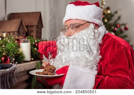 Portrait of cheerful Santa Claus taking milk from fireplace top secretly. He is standing and holding plate with cookies