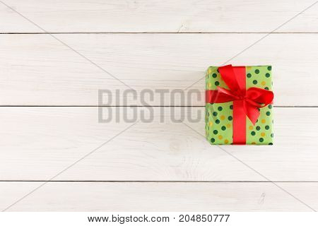 Top view on gift box in dotted wrapping paper tied with red satin ribbon on white rustic table with copy space. Christmas, birthday or valentine day present concept